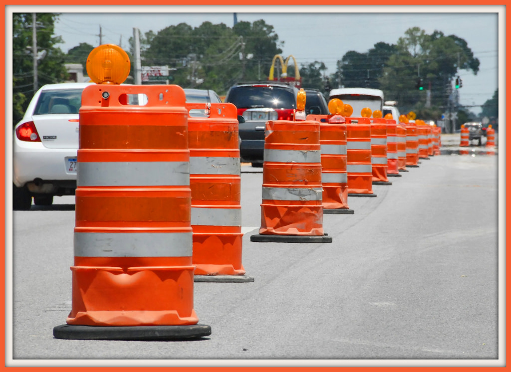Road construction barrels lining street